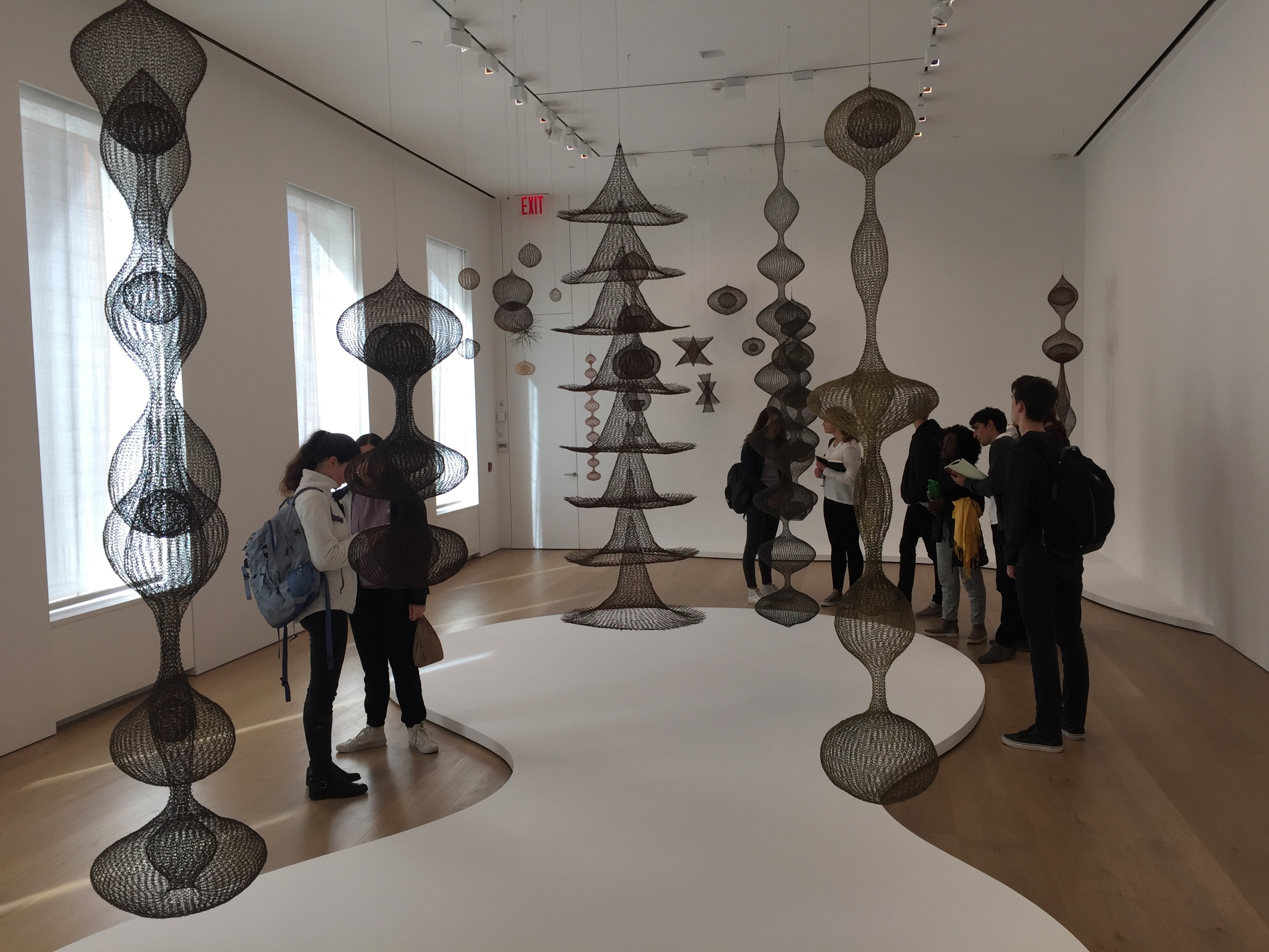Students making sketches and taking notes on Ruth Asawa's works.